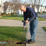 man checking the in-ground water valve in yard