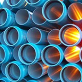 Generic image of a stack of light blue drainage pipes.