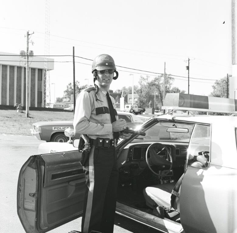 Image of a police officer standing next to a squad car.