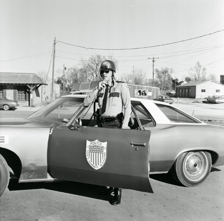 Image of a police officer standing next to a squad car using car radio.