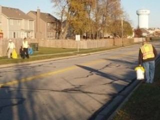 Image of Adopt-A-Street volunteers removing litter from a residential street.